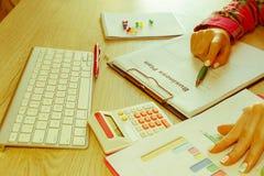 Osoby kobieta wskazuje writing cele na papierze, writing plan biznesowy przy miejscem pracy, Żeńscy mień pióra, papiery, notatki  Zdjęcia Stock