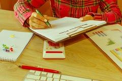 Osoby kobieta wskazuje writing cele na papierze, writing plan biznesowy przy miejscem pracy, Żeńscy mień pióra, papiery, notatki  Obrazy Stock
