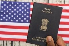 Osoby mienia Indiański paszport z ręką na USA lub flagą amerykańską jako tło zdjęcia stock