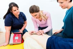 Osoby obecne pierwszej pomocy klasy uczenie dlaczego używać defibrillator zdjęcia stock