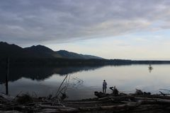 Osoby pozycja na krawędzi jeziora przy zmierzchem Obrazy Royalty Free