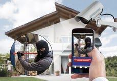 Osoby ręki mienia telefon komórkowy Wykrywa włamywacza Obrazy Royalty Free
