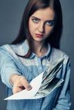 Osoby ` s ręka daje łapówce w dolarach ręka amerykańscy dolary Kobieta oferuje pieniądze na ciemnym tle 22 pocisków kaliberu dług Fotografia Stock