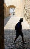 Osoby sylwetka jest ubranym kapeluszu i plecaka odprowadzenia puszek przy tłem stara ulica z kamiennym łukiem zdjęcia stock