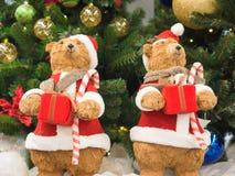 Osos del juguete vestidos como situación de Santa Clauses contra las cajas del árbol de navidad de un regalo de la tenencia imagen de archivo libre de regalías