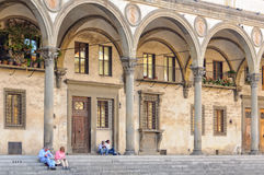 Ospedale degli Innocenti - Florence. Tourists and locals rest on the stairs and under  the arcade of the Hospital of the Innocents Ospedale delli Innocenti Royalty Free Stock Image