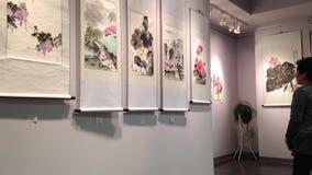 Ospite che ammira circa la pittura del cinese tradizionale stock footage
