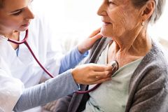 Ospite di salute e una donna senior durante la visita domestica Fotografie Stock Libere da Diritti