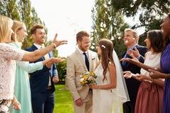 Ospiti che gettano i coriandoli sopra la sposa e lo sposo At Wedding fotografie stock libere da diritti