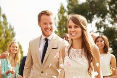 Ospiti che gettano i coriandoli sopra la sposa e lo sposo At Wedding Immagini Stock Libere da Diritti