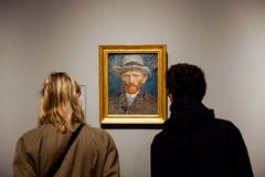 Ospiti che guardano il materiale illustrativo dell'autoritratto del pittore famoso Vincent van Gogh in Rijsmuseum nella città di  Fotografia Stock Libera da Diritti