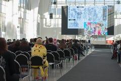 Ospiti che si siedono e che guardano flusso continuo sullo schermo di proiezione fotografie stock libere da diritti