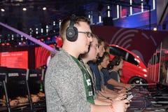 Ospiti della fiera campionaria che giocano il gioco delle automobili 2 di progetto a Gamescom immagini stock