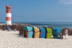 Ospiti della spiaggia nelle sedie di spiaggia variopinte alla duna tedesca dell'isola Fotografia Stock
