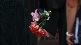 Ospiti di cerimonia che tengono i mazzi di bei fiori, regali di congratulazioni stock footage