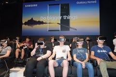 Ospiti di seduta che guardano un gioco da una cuffia avricolare di realtà virtuale fotografie stock