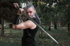 сosplay, dressed like a hero Geralt of Rivia from the game the Witcher, a fantastic warrior with a sword in his hands. Stock Photo