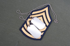 Oss armélikformig med tomma hundetiketter och den frodiga lappen för sergeant Arkivbilder