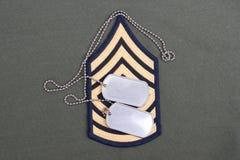 Oss armélikformig med tomma hundetiketter och den frodiga lappen för sergeant Royaltyfri Fotografi