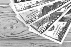 Oss dollar på vit svartvit plankabakgrund Arkivfoto