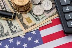 Oss flagga, dollarsedlar, oss centmynt, penna och räknemaskin Fotografering för Bildbyråer