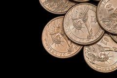 oss myntdollar som isoleras på svart Arkivfoton