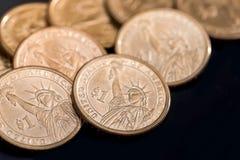 oss myntdollar som isoleras på svart Arkivbilder