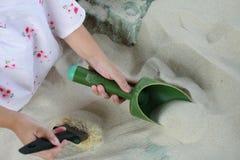 Ossa e fossili di dinosauro che scavano modello nella sabbia Immagine Stock