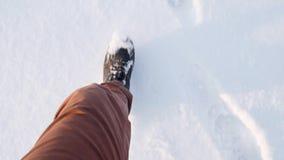 Osservando giù i piedi del ` s degli uomini che camminano attraverso la neve profonda, in stivali e jeans Movimento lento stock footage