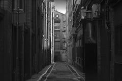 Osservando giù un vicolo lungo della parte posteriore di oscurità Fotografia Stock