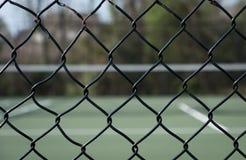 Osservando tramite il recinto il campo da tennis Immagine Stock