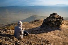 Osservare di seduta e leggente di una donna fuori la bella vista naturale fotografia stock