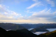 Osservi alla catena di montagne con i picchi medii delle nuvole Fotografia Stock Libera da Diritti