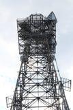 Osservi cercare una torre di antenna alta delle cellule di comunicazioni contro un cielo leggero Fotografia Stock