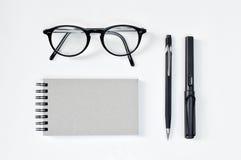 Osservi i vetri, il blocco note in bianco, la penna e la matita meccanica Immagine Stock Libera da Diritti