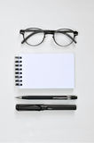 Osservi i vetri, il blocco note in bianco, la penna e la matita meccanica Immagini Stock