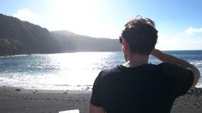 Osservi il colpo livellato dell'uomo che cammina accanto alla spiaggia stock footage