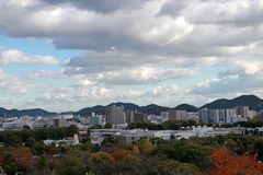 Osservi il paesaggio della città di Himeji con il fondo del cielo blu e della catena montuosa Fotografia Stock