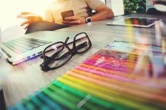 Osservi il vetro sullo scrittorio di legno con il progettista del sito Web che lavora la t digitale fotografie stock