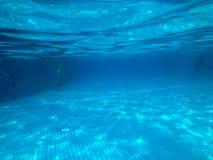Osservi la piscina con le piastrelle di ceramica sotto l'acqua blu, il punto di vista subacqueo della gente nello stagno in un ce immagine stock