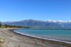 Osservi la spiaggia Kaikoura per nevicare sulle alpi del sud NZ Fotografia Stock