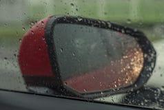 Osservi lo specchio dall'interno dell'automobile sulla pioggia del giorno con goccia di pioggia Immagini Stock Libere da Diritti
