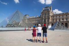 Osservi sulla piramide del Louvre a Parigi e su tre giovani con i ber Fotografie Stock Libere da Diritti