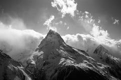 Osservi sulle nuvole del picco di alte montagne al sole Fotografia Stock
