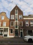 Osservi una vecchia casa di pietra con gli otturatori sulle finestre in tempo nuvoloso con le nuvole nella città di Vlaardingen immagine stock