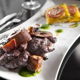 Osso Bucco. With polenta cakes and green sauce Royalty Free Stock Images