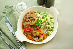 Osso Bucco And Rice. Slow roasted osso bucco with a green pea rice ready to serve Stock Photo