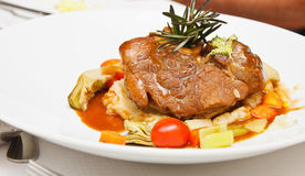 Osso Bucco on White Plate. Veal shank roasted and served on braised vegetables Stock Image