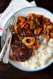 Osso buco炖牛肉用在西红柿酱的煮沸的米与葱、红萝卜、芹菜、大蒜、迷迭香和月桂树叶子 库存图片