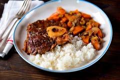 Osso buco炖牛肉用在西红柿酱的煮沸的米与葱、红萝卜、芹菜、大蒜、迷迭香和月桂树叶子 免版税库存图片